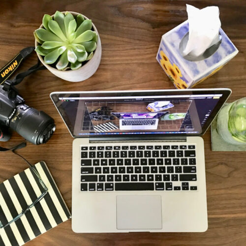 Flatlay of MacBook, succulent, camera, notebook, glasses, cucumber water and tissues.
