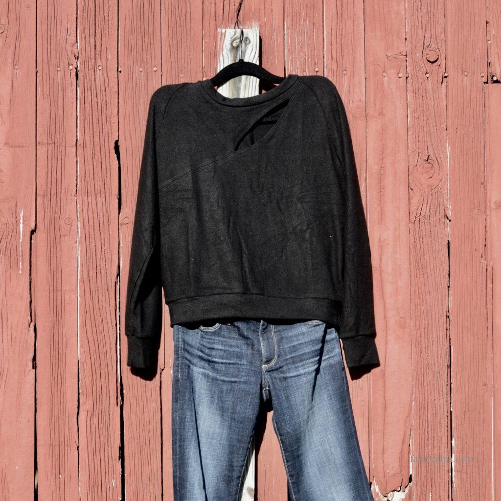 Black sweatshirt with asymmetric cut-out.