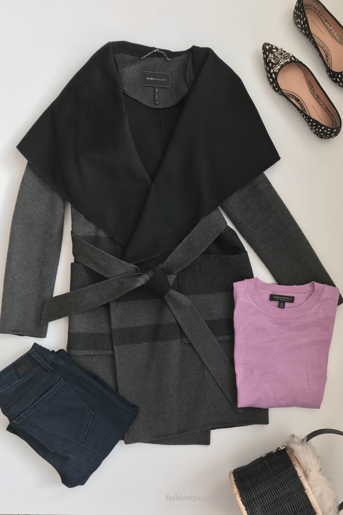Flatlay of gray shawl collar coat, lavender sweater, jeans, flat shoes, drop earrings and basket bag with fur trim.