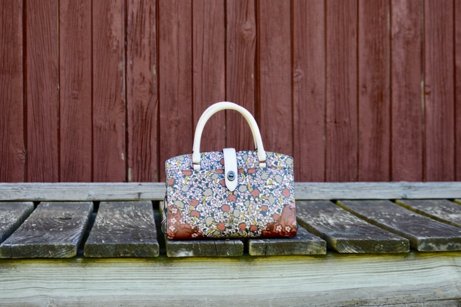 Cream and red printed top-handle bag in front of a barn wall.