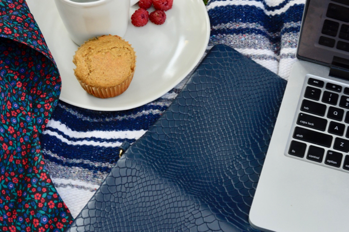 Flatlay of Macbook, laptop clutch, muffin, and floral print jacket.