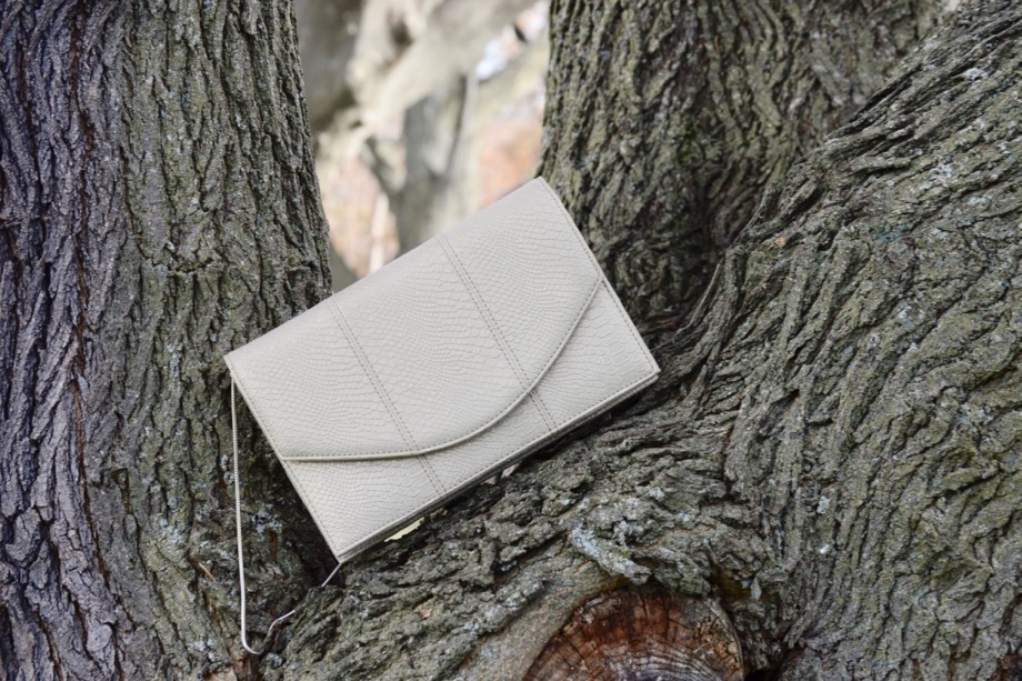 Light gold envelope bag on a tree branch.