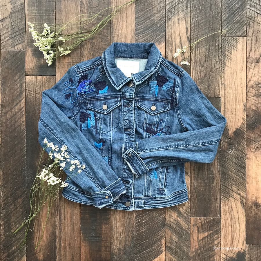 Denim jacket with embroidery flatlay on wood floor. Winter To Spring Transition Piece.