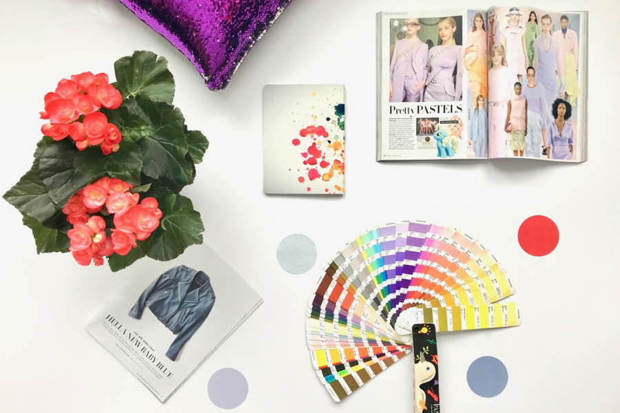 Flatlay of Pantone color fan, notebook, magazines, red flowers, purple cushion and dots of color.