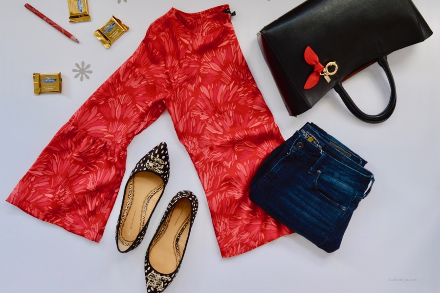 Flatlay of red blouse, pointed ballet flats, jeans, tote bag and chocolate.