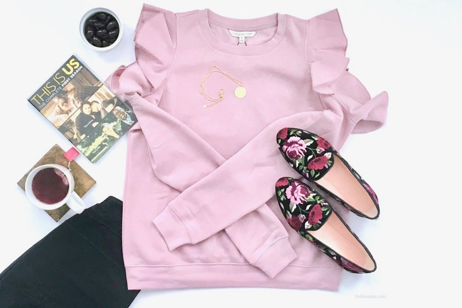 Flatlay of pink ruffle sleeve sweatshirt, embroidered shoes, jeans, tea, DVD and chocolate almonds.