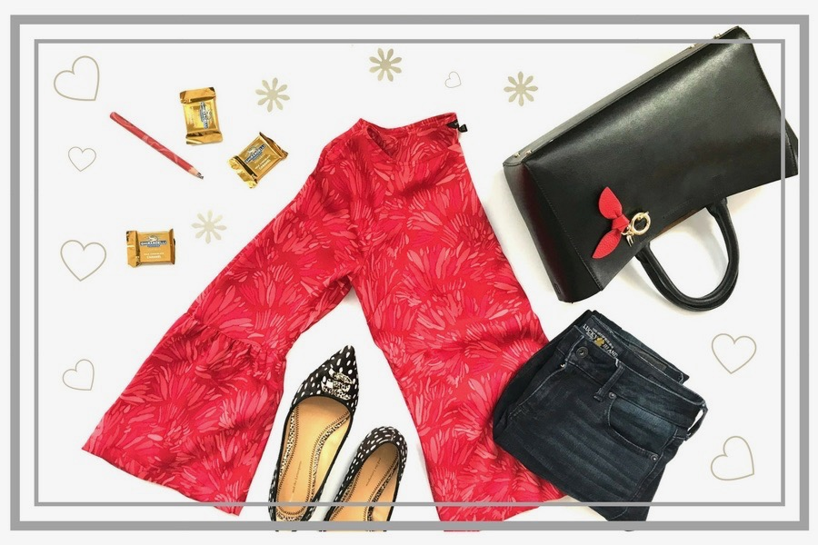 Flatlay of red bell sleeve top, black tote, jeans, ballet flats, chocolate, pencil, hearts and flowers.