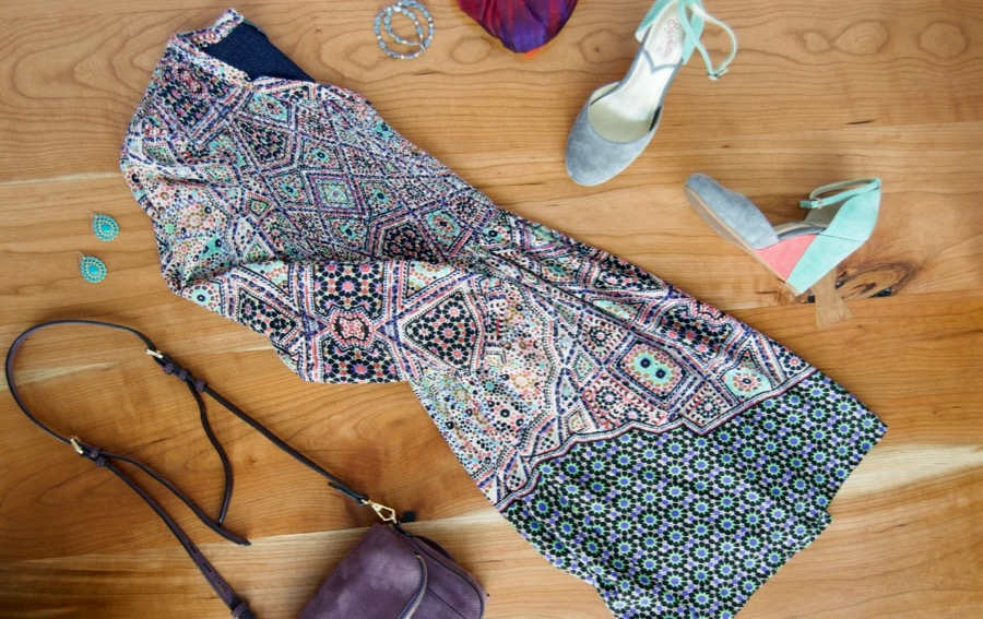 Flatlay of patchwork print dress, wedge shoes, purple handbag and turquoise earrings.