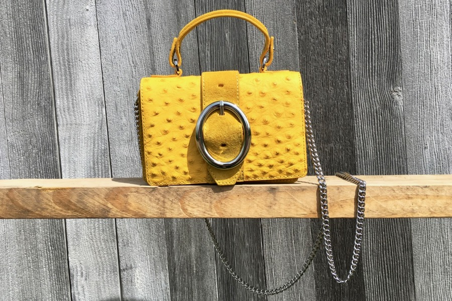 Yellow handbag with silver chain and oval buckle.