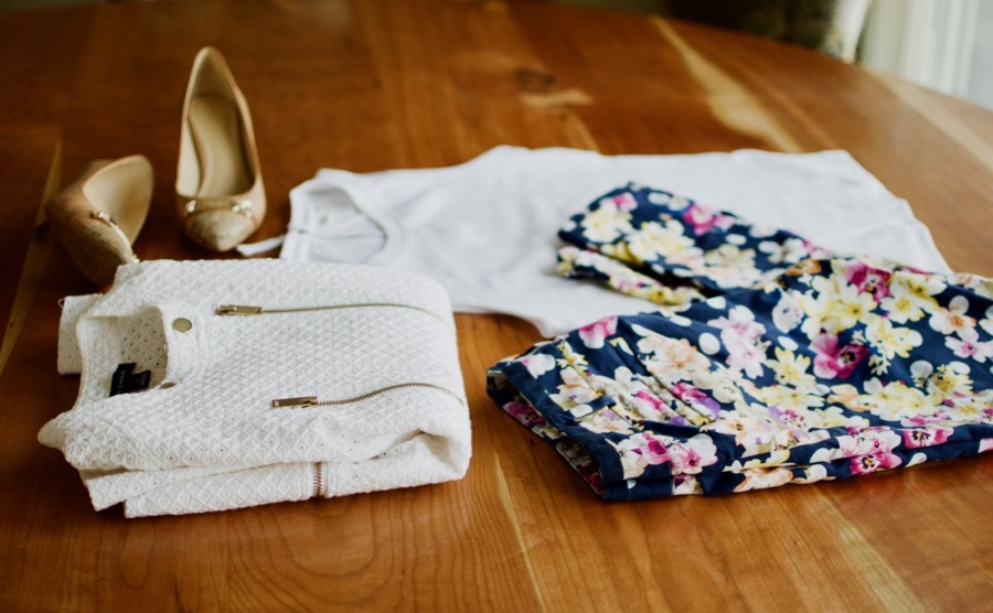 Flatlay of floral pants, textured jacket, white t-shirt, and neutral pumps.
